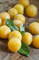 ameixas maduras amarelas sobre fundo de madeira velha foto