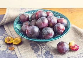 ameixas roxas em um prato verde foto