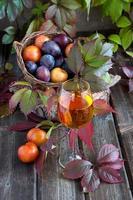 saborosas ameixas e copo de vinho foto