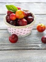 cesta de vime cheia de ameixas maduras foto