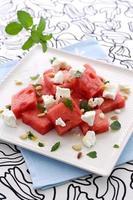 uma salada de feta de melancia num prato quadrado branco foto
