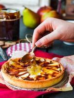 torta de maçã com geléia de pêra despeje caramelo, mãos foto