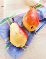peras frescas em uma mesa de madeira foto