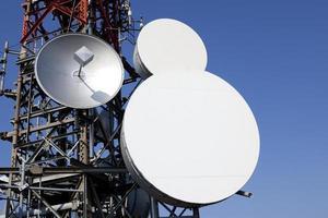 antenas parabólicas na torre de telecomunicações foto