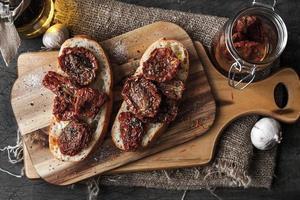 tomate seco no pão branco na placa de madeira foto