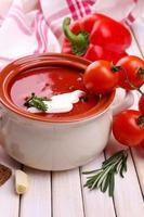 sopa de tomate saboroso e legumes na mesa de madeira foto