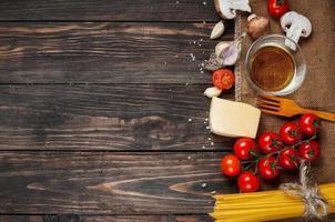 macarrão, tomate e cogumelos no fundo da mesa de madeira com cópia foto
