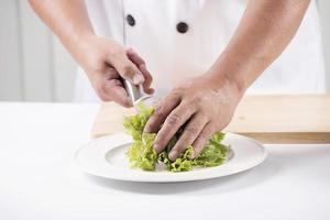 mãos do chef cortar alface foto