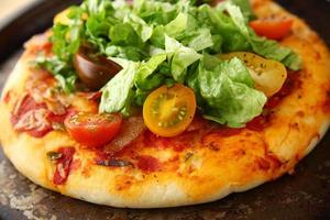 pizza com bacon, alface e tomate fresco foto