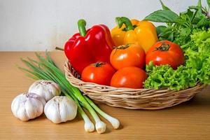 legumes orgânicos na cesta de vime em fundo de madeira foto