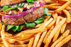 hambúrguer e batatas fritas fechem sobre fundo de madeira.