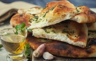 pão fresco caseiro e especiarias sobre uma mesa. foto