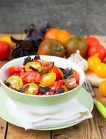 salada de tomates coloridos em um fundo de madeira foto