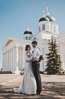 o casal está de pé na frente das colunas brancas foto