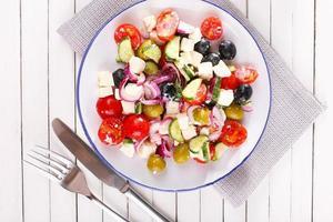 salada grega servida em prato guardanapo com fundo de madeira