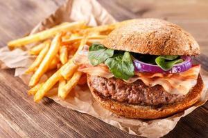hambúrguer e batatas fritas fechem sobre fundo de madeira. foto
