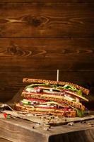 sanduíche no velho papper com grande placa de corte foto