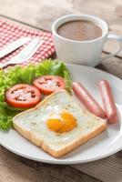 café da manhã, ovo em um buraco com lingüiça e café. foto