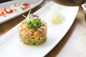 pilha de tártaro de salmão com abacate, azeitonas e estragão foto
