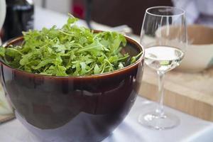 rúcula em uma tigela e um copo de vinho. foto