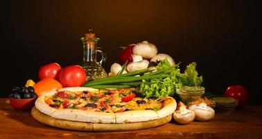 massa de pizza deliciosa, temperos e legumes na mesa de madeira foto
