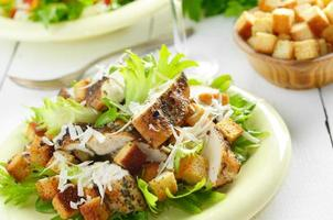 salada de frango caesar na mesa branca foto