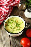 xícara de sopa no fundo de madeira marrom foto