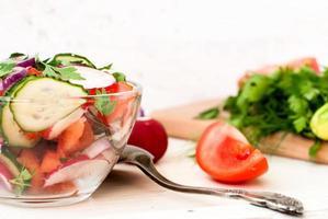 salada primavera com rabanetes, pepino, repolho e cebola close-up foto