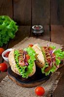 cachorro-quente com mostarda de ketchup e alface em fundo de madeira. foto