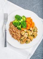 trigo sarraceno com carne e legumes em um prato branco