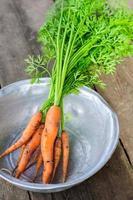 cenoura fresca não lavada em tigela no fundo de madeira velho foto