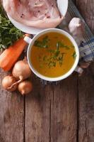 caldo de galinha e ingredientes. vista superior vertical, caseira foto