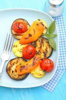 legumes grelhados (abobrinha, pimentão, tomate) em um prato azul foto