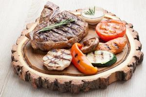 porção de bife de churrasco com molho e legumes grelhados foto