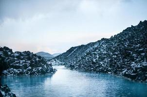 Rocha, água, neve, céu. foto