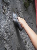 mão pendurado na rocha na escalada foto