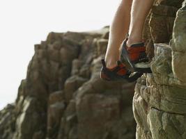 pés de alpinistas na face íngreme da rocha foto