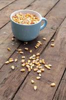 grãos de milho na mesa de madeira foto