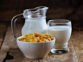 flocos de milho em uma tigela e copo de leite na mesa de madeira foto