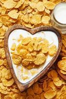 café da manhã saudável: flocos de milho com leite em uma tigela de madeira foto