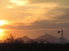 moinho de vento no deserto ao pôr do sol foto