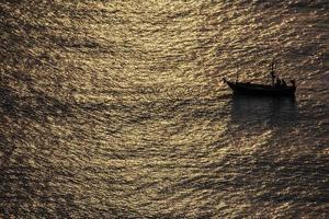 barco de pesca no mar dourado no meio do mar da Tailândia foto
