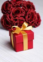 flores vermelhas e caixa de presente com fita amarela foto