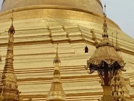 monge cercado por pagode dourado foto
