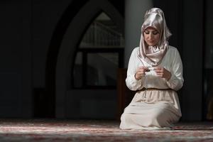 mulher muçulmana está rezando na mesquita foto