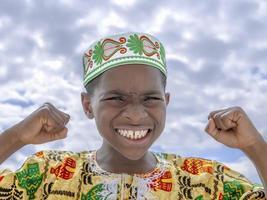 menino afro rugindo, punhos cerrados foto