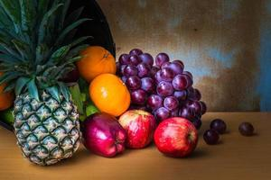 abacaxi e frutas em uma madeira foto