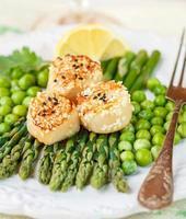 delicioso jantar de vieiras assadas, aspargos e ervilhas verdes foto