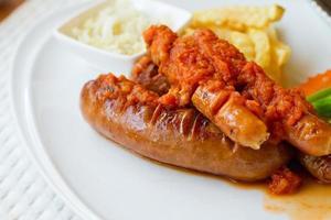 prato de salsicha com batata frita e vegetais foto
