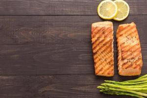 salmão grelhado com limão, aspargos em fundo de madeira
